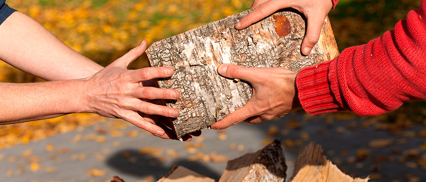Hands passing wood from wood pile