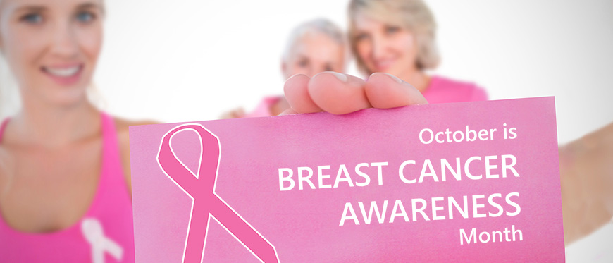 Women in pink holding up October is Breast Cancer Awareness Month Sign