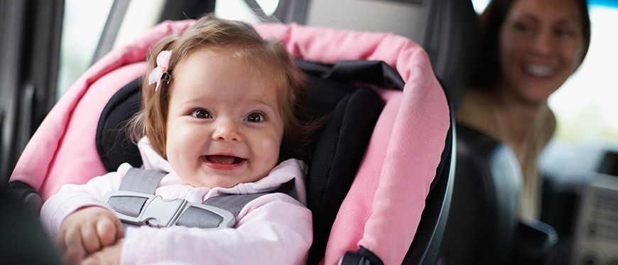 A toddler in a car seat with her mom looking back at her
