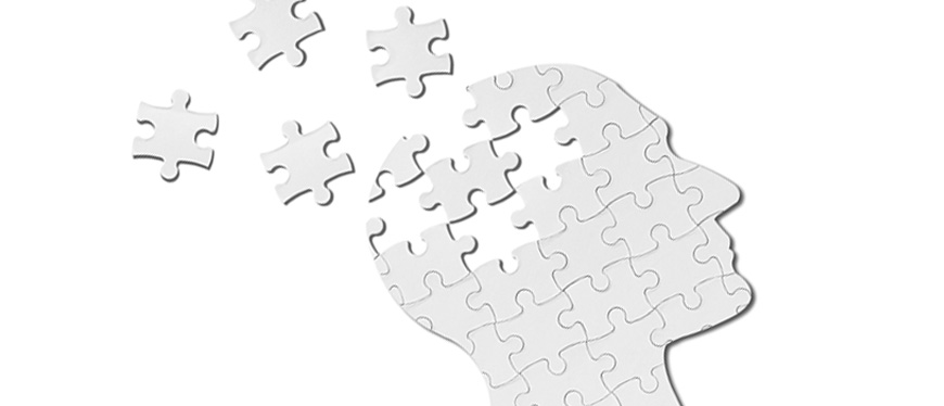 Human head made out of puzzle pieces with several pieces flying away