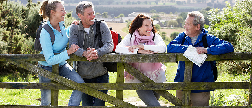 Two mature couples out for spring hike leaning on fence