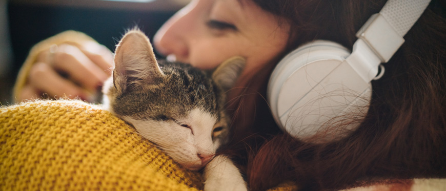 Woman with headphones on snugging a kitten
