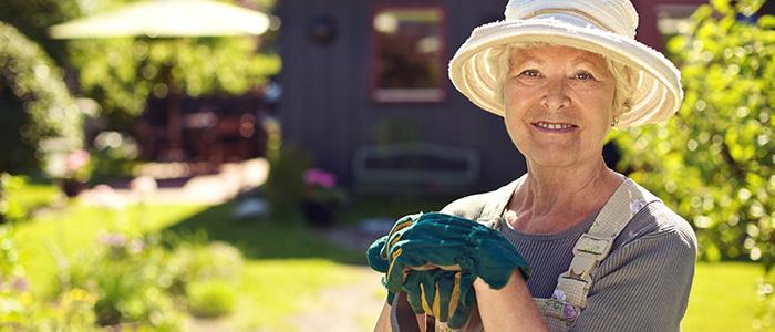 Senior woman leaning on a garden shovel