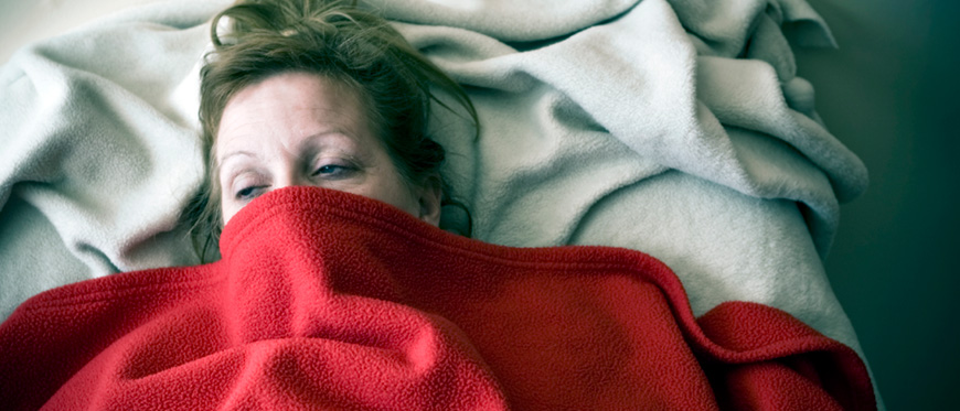 Woman in bed sick with face partially covered by blanket