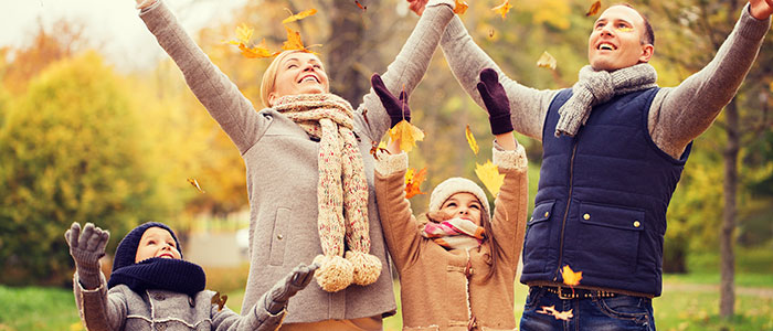 Family outdoors with upstretched arms