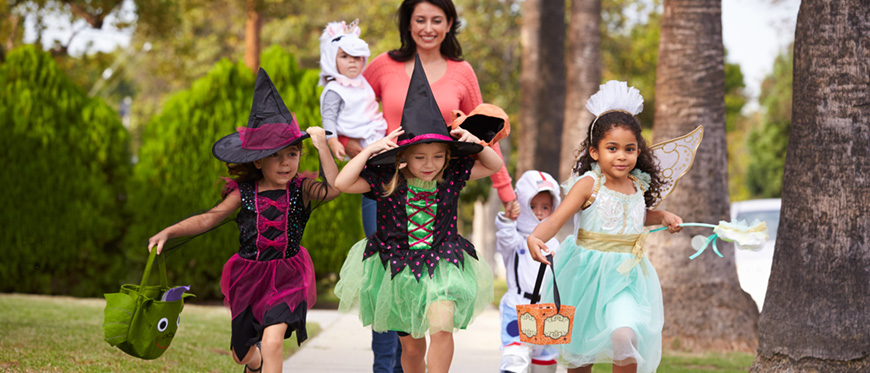 Three girls dressed in witch and princess costumes trick or treating with their mom
