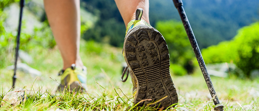 Close up of girl's legs and muddy sneakers hiking with poles