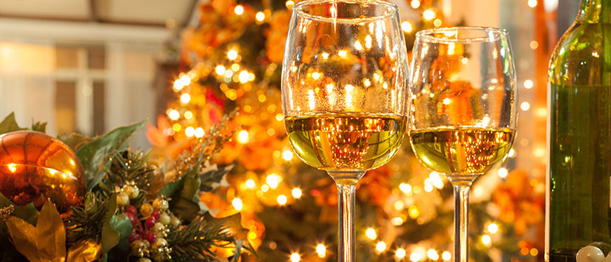 Two glasses of white wine and wine bottle on table in front of christmas tree