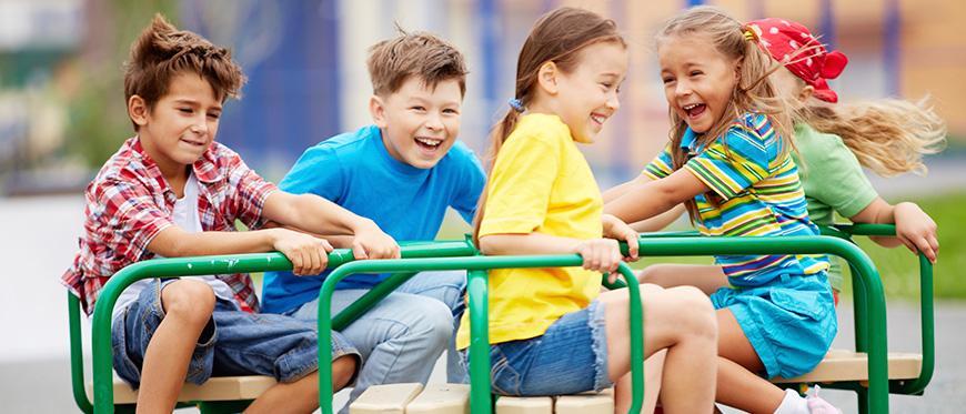 Grade school children playing on playgound merry-go-round