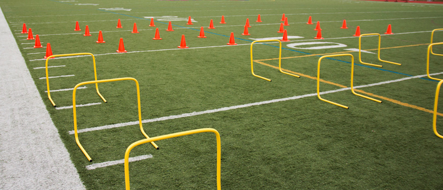 Football field set up with agility course for training.