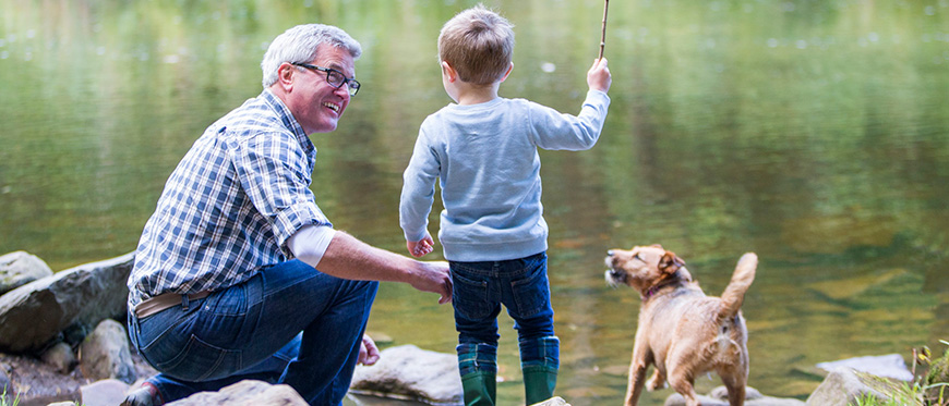 Grandfather playing with grandson and dog by a river