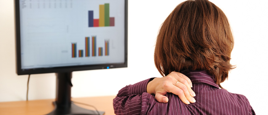 Woman holder her shoulder while looking at computer monitor