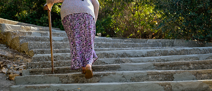 Older woman walking up flight of stone steps using cane