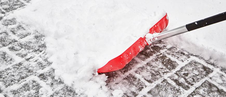 Red snow shovel pushing snow