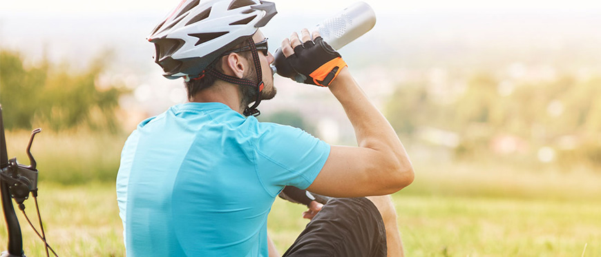 Male cyclists sitting next to bike drinking water from water bottle