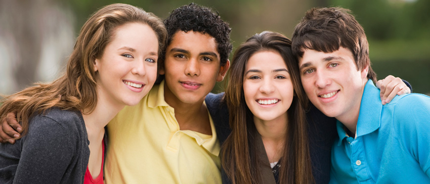 Four teenagers with arms around each other's shoulders