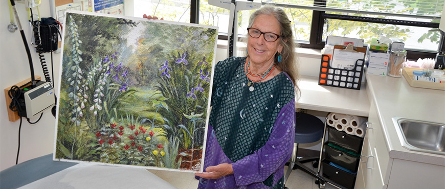 Andrea Triguba, RN holding up a ceiling tile she painted of a garden
