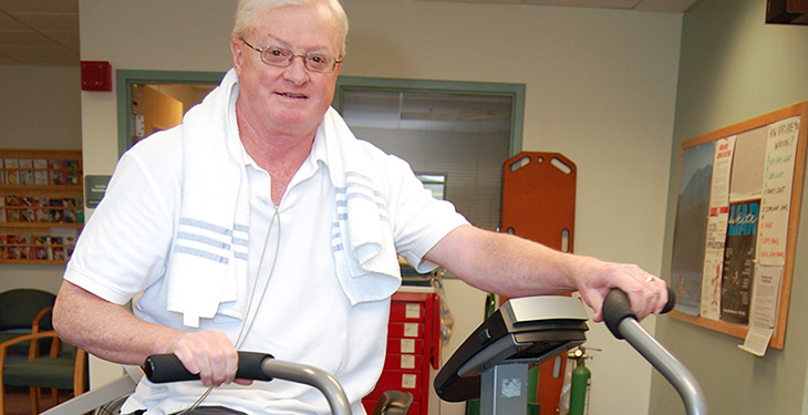 Older man riding a stationary bike