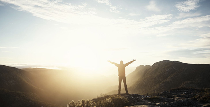 Man standing with arms out at top of mountain at sunrise