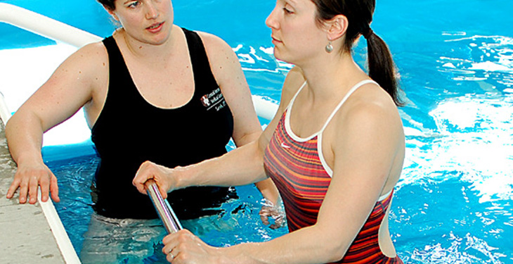 Aquatic therapist working with patient in pool