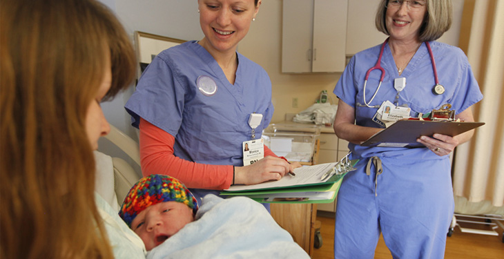 Nurses talking with mother holding newborn
