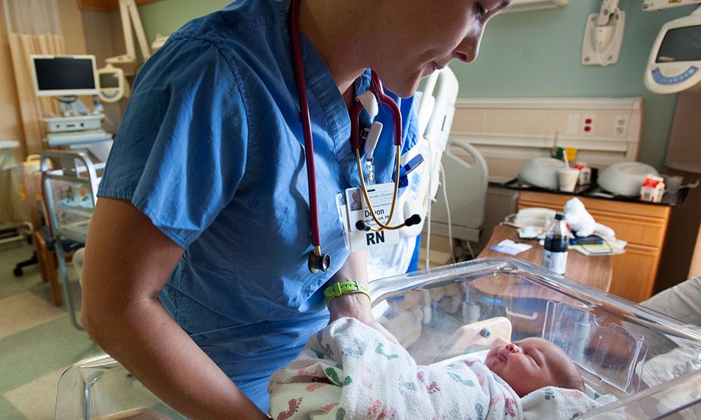 Nurse returning newborn to crib in new mom's private room