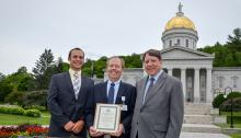 Tim Perrin, Richard Morley and Leo Martino hold Governor's Award for Environment Excellence in front of state house