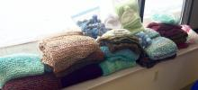 Stacks of shawls, afghans, lap robes, hats, blankets, and stress balls knitted for patients