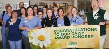 Group of CVMC nurses hold up Daisy Award banner