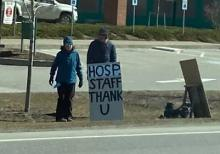 Two central Vermont community members outside of CVMC with sign thanking hospital workers